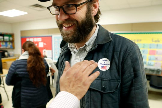 Democrat Jamie Wilson gets a sticker after voting in the Texas primary Tuesday in Dallas. A total of 14 states, including Arkansas, held primary elections on Tuesday.