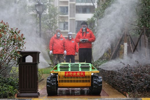 Volunteers spray disinfectant with a robot at a residental area in Wuhan in China's central Hubei province on March 3, 2020.   The world has entered uncharted territory in its battle against the deadly coronavirus, the UN health agency warned, as new infections dropped dramatically in China on March 3 but surged abroad with the US death toll rising to six.