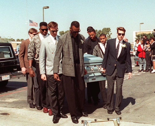 Members of the Loyola Marymount basketball team carry the coffin of teammate Hank Gathers into the school gym for a memorial service two days after his death.