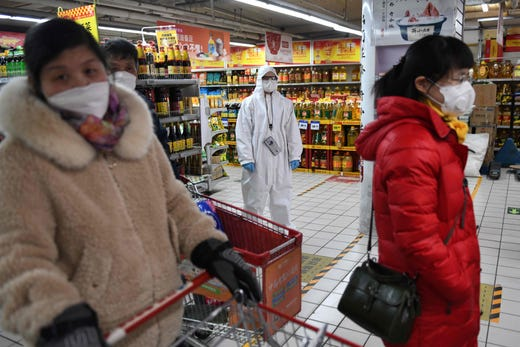 A worker wears protective clothing as a preventive measure against the COVID-19 coronavirus as she watches over customers in a supermarket in Beijing on March 3, 2020.