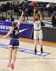 ACU's Dominique Golightly (3) shoots a 3-point goal over Stephen F. Austin's Riley Harvey in the first half. Golightly tied a single-game school record with nine 3s. The Wildcats beat SFA 88-62 in the Southland Conference game Tuesday at Moody Coliseum.