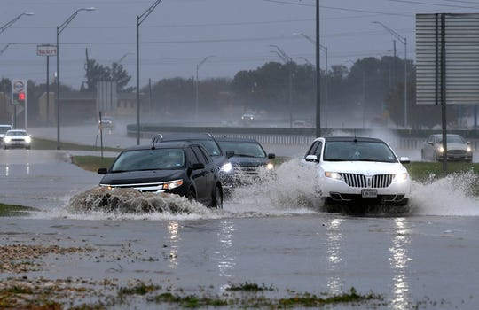 Vehicles travel down a swamped stretch of South Clack Street between Catclaw Drive and South 27th Street on March 4.