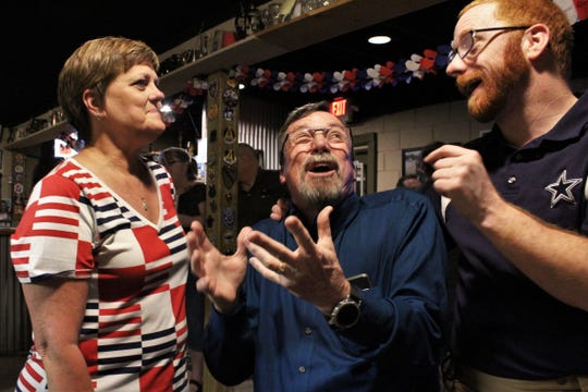 Justice of the Peace Mike McAuliffe, center, jokes about coaching Brian Woodyard, right, in youth baseball while Sherri McAuliffe, his wife, smiles at their animated conversation at Pappy Slokum Brewery on Tuesday night. McAuliffe, the former Abilene Police Department officer, kept his Precinct 1, Place 1 seat by defeating Shawna Joiner.