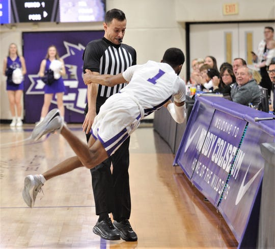 ACU's Reggie Miller (1) tries to make a save on a loose ball without colliding with an official during the first half of the Wildcats' game against Stephen F. Austin. Miller was unsuccessful on the play, and it went for an ACU turnover.