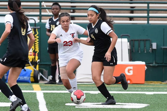 Abilene High's Amaris Amaya (4) works to keep the ball away from Euless Trinity's Jadyn Renteria (23) during Tuesdays game at Shotwell Stadium. Amaya helped set up the only Lady Eagle goal in the 6-1 loss.