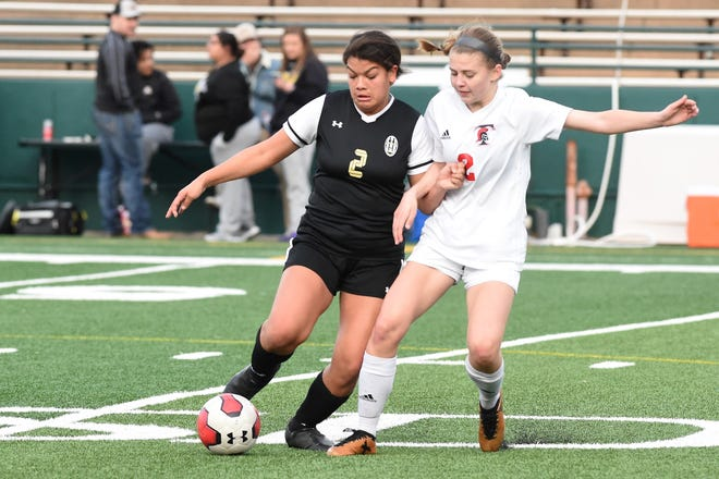 Abilene High's Jocelyn Reece (2) keeps the ball from Euless Trinity's Avery Seaman (2) during the March 3 game at Shotwell Stadium.