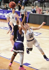 ACU's Breanna Wright (10) drives past Stephen F. Austin's Kennedy Harris for a layup in the first half.