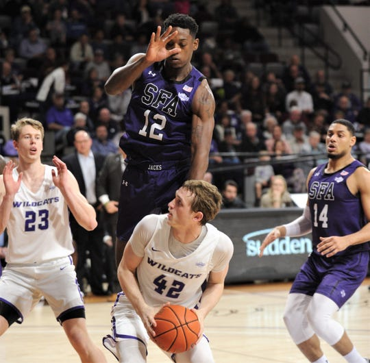 ACU's Clay Gayman (42) is fouled by Stephen F. Austin's Charlie Daniels (12) in the first half. Gayman scored 16 of his team-high 17 points in the half. SFA won the game 77-72 on Tuesday at Moody Coliseum.