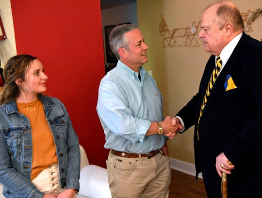 Kevin Willhelm shakes hands with Dave Crymes as the candidate's daughter, Ella, watches Tuesday. Willhelm was watching the election returns for his 104th District Court judge race with supporters at the Wooten. He will face Jeff Propst in a runoff.