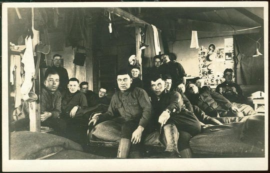 Postcard showing a photo of soldiers relaxing in the barracks at Camp Custer, c. 1918.