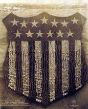 "In 1918, 30,000 military troops at Camp Custer posed in ""The Human U.S. Shield"" for artists Arthur S. Mole and John D. Thomas."
