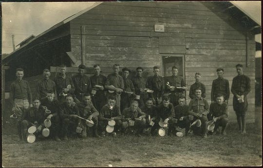 Postcard showing a group of soldiers with their mess kits outside a building at Camp Custer, c. 1918
