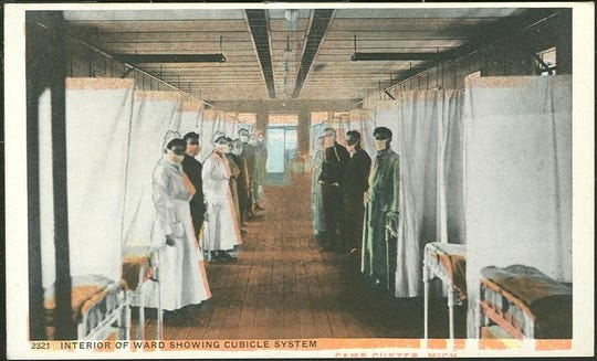 A color postcard showing the interior of the Camp Custer hospital ward in 1918. A total of 674 soldiers stationed died as a result of the Spanish Flu in the fall of that year.