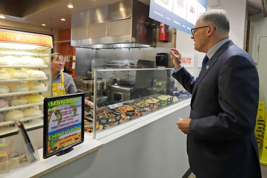 Washington Gov. Jay Inslee, right, orders food at the Uwajimaya Asian Food and Gift Market, Tuesday, March 3, 2020, in Seattle's International District. Inslee said the visit was to encourage people to keep patronizing businesses during the COVID-19 Coronavirus outbreak.