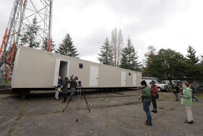 Reporters and photographers work Tuesday, March 3, 2020, at the site in South Seattle where King County will be placing several temporary housing units like the one shown here to house patients undergoing treatment and isolation in response to the COVID-19 coronavirus.
