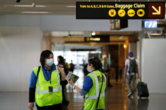 A pair of workers at Seattle-Tacoma International Airport wear masks Tuesday, March 3, 2020, in SeaTac.