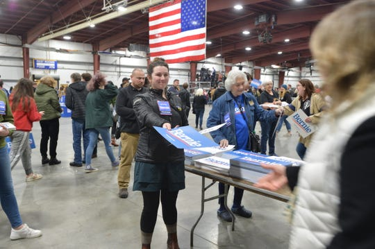 Holly Bahnsen of Burlington hands Bernie Sanders signs to rally goers at the Super Tuesday rally in Essex Junction on March 3, 2020.
