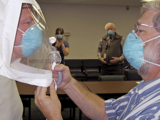Flu prep in 2007: Burlington resident Bryan Wemple, left, has his blue N95 mask tested for a tight fit by Andy Squires of Richmond on Oct. 9, 2007. Wemple's plastic head covering is designed to concentrate a scented mist — which, if detected, means that the blue mask is not fitted properly. The exercise in South Burlington was part of a flu-preparedness workshop organized by Chittenden County's Local Emergency Planning Committee. Squires said his facial hair would reduce the effectiveness of his mask during exposure to a genuine health threat: anything more than a two-day stubble is risky.