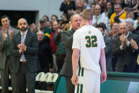 Vermont head coach John Becker hugs Josh Speidel (32) as he comes off the court during the men's basketball game between the Albany Great Danes and the Vermont Catamounts at Patrick Gym on Tuesday night March 3, 2020 in Burlington, Vermont.