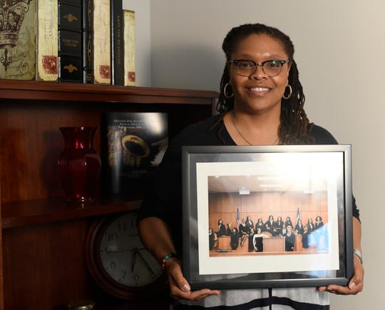 Harris County Judge Shannon Baldwin poses with a photo of the 19 elected black women in Harris County after the 2018 election, Tuesday, Feb. 18, 2020, in Houston. Baldwin is the Harris County criminal court number 4 judge.