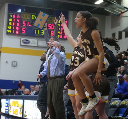 Roger Bacon's bench reacts after Kelly Brenner hits a 3-pointer to give the Spartans the lead during their regional semifinal win over Jonathan Alder, Tuesday, March, 3, 2020.