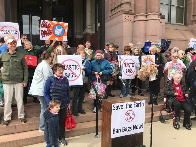 About 60 protesters gathered Wednesday afternoon on the steps of City Hall, calling for a citywide ban on disposable plastic bags