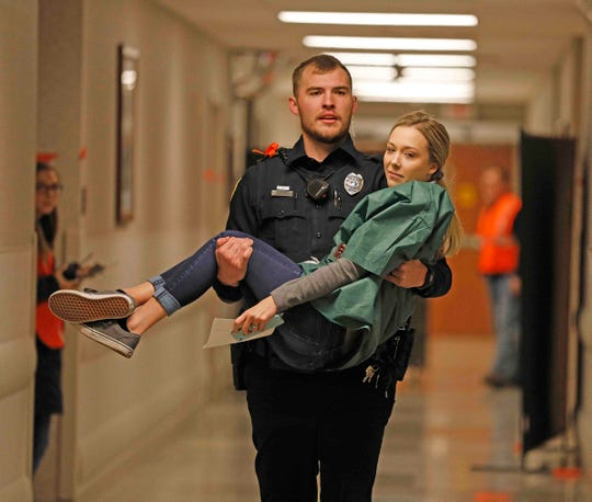 """Pictured: a role player being carried by an officer to the emergency room for """"treatment"""" during the critical incident exercise."""