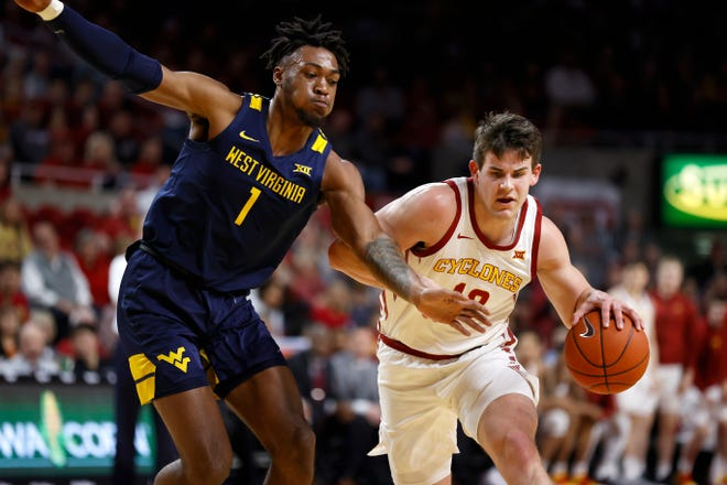 Iowa State forward Michael Jacobson, right, drives to the basket as West Virginia forward Derek Culver defends during the first half of an NCAA college basketball game Tuesday, March 3, 2020, in Ames, Iowa. (AP Photo/Matthew Putney)