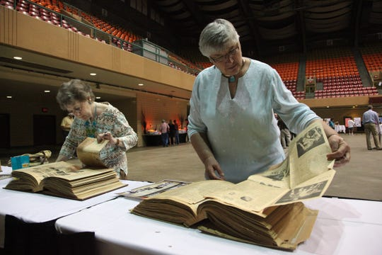 """Teresa Parmenter of Des Moines  and Betty Jane """"BJ"""" Kearns of Kelley, look through scrap books on display at Veterans Memorial Auditorium in 2010. Parmenter spent the night at Vets back in 1959 when the Basketball tournament was snowed in."""