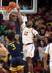 Iowa State forward Solomon Young, right, blocks a shot by West Virginia forward Gabe Osabuohien during the first half of an NCAA college basketball game Tuesday, March 3, 2020, in Ames, Iowa. (AP Photo/Matthew Putney)