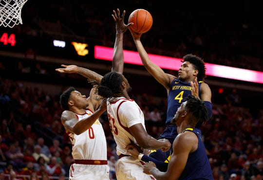 West Virginia guard Miles McBride, right, shoots over Iowa State forwards Zion Griffin, left, and Solomon Young during the second half of an NCAA college basketball game Tuesday, March 3, 2020, in Ames, Iowa. West Virginia won 77-71.