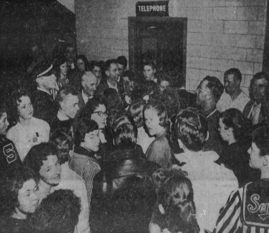 Girls' basketball fans crowd around a telephone booth at Veterans Memorial Auditorium to call home after an announcement was made that a snowstorm would keep out-of-towners from leaving the city.
