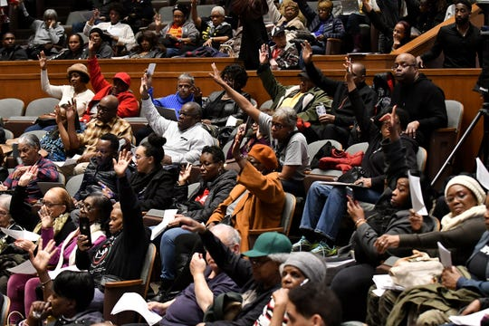 People in attendance raise their hands showing that they are homeowners as Detroit's city council holds a public hearing regarding overtaxation of homeowners at the Coleman A. Young Municipal Center in Detroit on Tuesday.