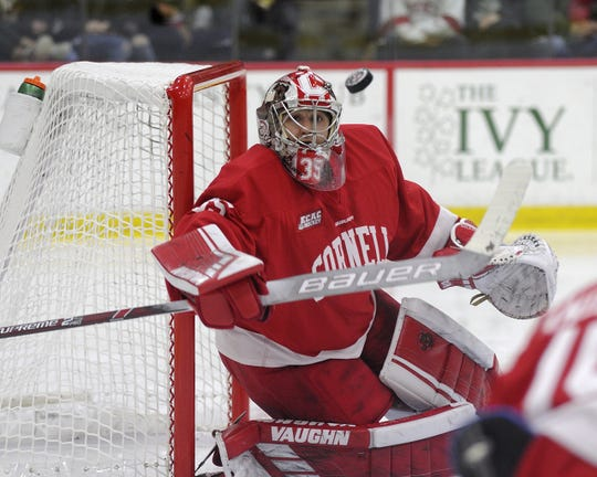 Matthew Galajda directs a shot to the corner with his blocker during the Cornell men's hockey team's 3-1 victory against Harvard on Dec. 6, 2019 at Bright-Landry Hockey Center in Cambridge, Mass.