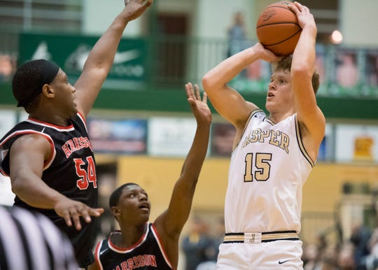 Jasper's Jackson Kabrick (15) takes a shot guarded by Harrison's Ja'Twan Watson (54) as the Jasper Wildcats play the Harrison Warriors during the first round of the IHSAA Class 4A boys basketball sectionals at North High School in Evansville, Ind., Tuesday evening, March 3, 2020.