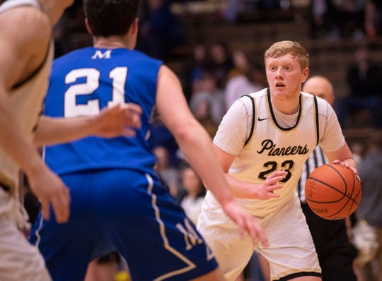Boonville's Hunter Bruce (23) looks for a teammate while being guarded by Memorial's Cade Graham (21) during the 2020 3A Basketball Sectional Tournament 32 at Boonville High School Tuesday night, March 3, 2020.