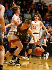 North Posey's Josiah Ricketts (30) trips over Mater Dei's Tyler Phelps (42) during the Class 2A boys basketball sectional opening round at Huntingburg Memorial Gymnasium in Huntingburg, Ind., Tuesday, March 3, 2020. The Vikings defeated the Wildcats, 66-58.