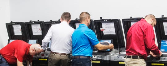 Staff for the Lee County Supervisor of Elections place test votes in a tabulator during a logic and accuracy testing in front of the Lee County canvassing board at the Lee County Elections Center in Fort Myers on Wednesday, March 4, 2020. The tabulators are ready to go for early voting and election day.