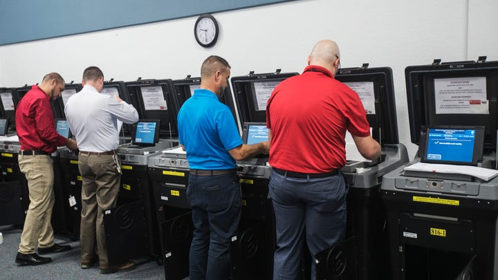 Staff for the the Lee County Supervisor of Elections place test votes in a tabulator during a  logic and accuracy testing in front of the Lee County cavassing board at the Lee County Elections Center in Fort Myers on Wednesday March, 4, 2020. The tabulators are ready to go for early voting and election day.