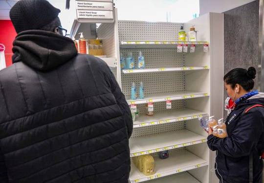 Shoppers at a Target store in Brooklyn face depleted shelves of hand sanitizers as concerns grow around COVID-19, Tuesday March 3, 2020, in New York. A man from New York City's suburbs was hospitalized in serious condition with COVID-19 on Tuesday, a case that prompted school closings and quarantines for congregants of a now-shuttered synagogue. The state's second confirmed case also raised the possibility that the virus is spreading locally. (AP Photo/Bebeto Matthews)