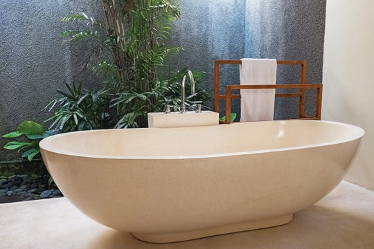 Luxury bathroom with stone bathtub and open space concept in a modern house or villa