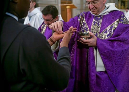 Faithful receive the holy communion into their hands during a Mass celebrated at Saint Francois Xavier church in Paris, France, Sunday, March 1, 2020. The archbishop of Paris is asking all of the French capital's parish priests to change the way they administer communion to counter the spread of the coronavirus.