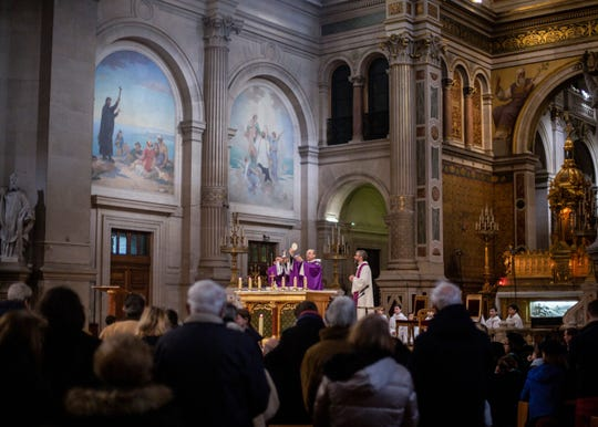 A priest prepares to give the Holy Communion to faithful during a Mass celebrated at Saint Francois Xavier church in Paris, France, Sunday, March 1, 2020.  The archbishop of Paris is asking all of the French capital's parish priests to change the way they administer communion to counter the spread of the coronavirus.