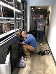 Hometown Roots owner Casey Todd coils water tubing for his new hydroponic growing system while hydroponic farmer Andy Seymour plumbs the new grow wall in the Downtown Henderson restaurant.