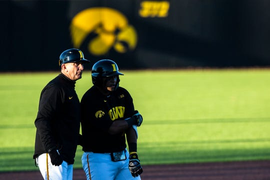 Iowa head coach Rick Heller, left, talks with Iowa's Izaya Fullard (20) during a non-conference game on March 3, 2020, at Duane Banks Field in Iowa City.