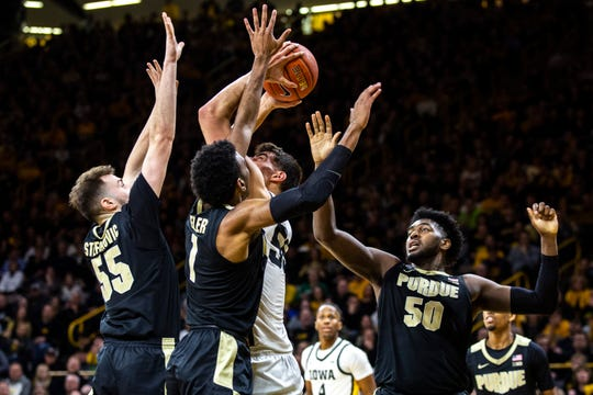 Iowa center Luka Garza, center, attempts to shoot a basket as Purdue's Sasha Stefanovic (55) Aaron Wheeler (1) and  Trevion Williams (50) defend during a NCAA Big Ten Conference men's basketball game, Tuesday, March 3, 2020, at Carver-Hawkeye Arena in Iowa City, Iowa.