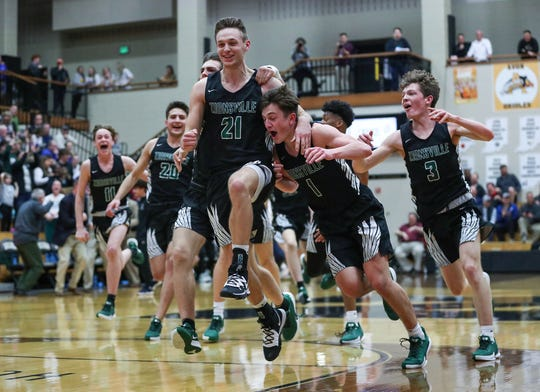 The Zionsville Eagles celebrate their sectionals win over Fishers at Noblesville High School on Tuesday, March. 3, 2020. Zionsville's Jackson Hughes (21) scored two points in the final seconds of the game to clinch the win, 23-21.