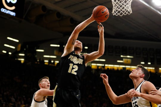 Purdue forward Evan Boudreaux drives to the basket over Iowa center Luka Garza, right, during the first half of an NCAA college basketball game, Tuesday, March 3, 2020, in Iowa City, Iowa. (AP Photo/Charlie Neibergall)