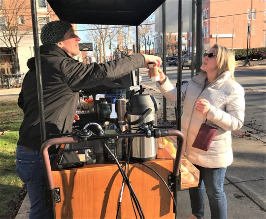 City resident Natalie Noyes buys a cup of coffee Wednesday morning from L-City Pop-Up Coffee, which was doing business at Broad and Main streets.