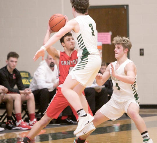 Canton's Ben Stesiak looks for an open man, guarded by Highlanders Will Hann and Peyton Ward Tuesday, March 3, 2020.